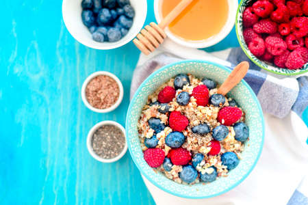 High protein healthy breakfast, buckwheat porridge with blueberries, raspberries, flax seeds and honey Closeup view Stock Photo - 111666096