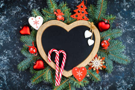 New Year's composition of Christmas tree branches and Christmas tree decorations and a frame in the shape of a heart, top view, place for text,