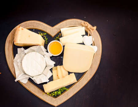 Various types of cheese on rustic wooden table Archivio Fotografico - 111665749