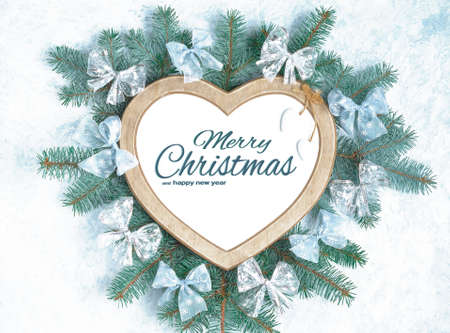 Christmas frame in the shape of a heart is surrounded by branches Stock Photo