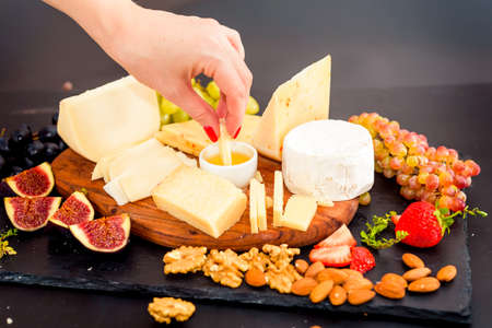 Cheese plate served with grapes, jam, figs, crackers and nuts Фото со стока