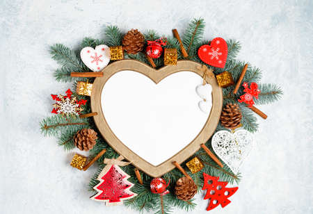 Christmas frame in the shape of a heart is surrounded by branches Banco de Imagens - 113043910