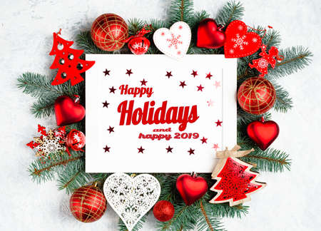 Happy Holidays and happy 2019 text with Christmas photo frame surrounded by branches of a New Year tree, red Christmas decorations. Stock Photo