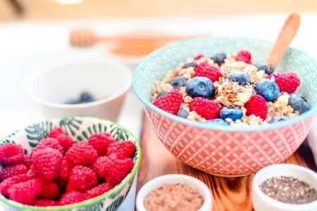 High protein healthy breakfast, buckwheat porridge with blueberries, raspberries, flax seeds and honey Closeup view, selective focus Stock Photo