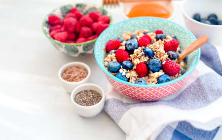 High protein healthy breakfast, buckwheat porridge with blueberries, raspberries, flax seeds and honey Closeup view, selective focus Stock Photo - 118403708
