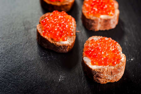 Red caviar on bread on slate background.