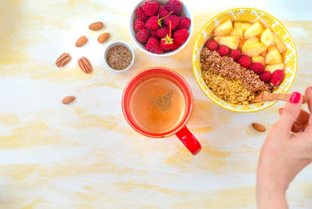 Top view, female hands holding a cup of coffee, a spoon with oatmeal, with honey nuts, raspberries, on a yellow wooden table Good morning - healthy breakfast background