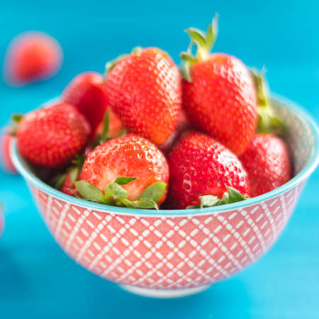 Fresh strawberries in bowl isolated on blue background