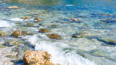 background of transparent sea water and bottom, with stones and waves 写真素材