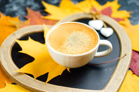 Autumn leafs and coffee cup on wooden table. Stock Photo