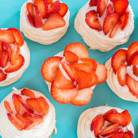 A small meringue Pavlova dessert with some strawberry slices on a blue background.