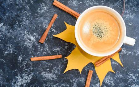 Autumn coffee composition, coffee cup with foam, cinnamon, autumn leaf at black background. 版權商用圖片