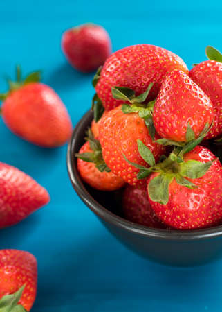 fresh bright strawberries in a bowl top view on blue background Reklamní fotografie