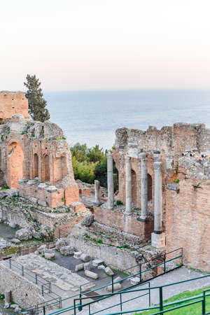 View of some columns and one arch in the scene of the greek theater in Taormina and a perspective of Giardini Naxos