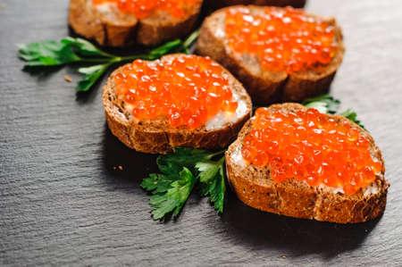Red caviar on bread on slate 写真素材