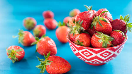 Colorful ripe strawberries in a bright bowl on a blue