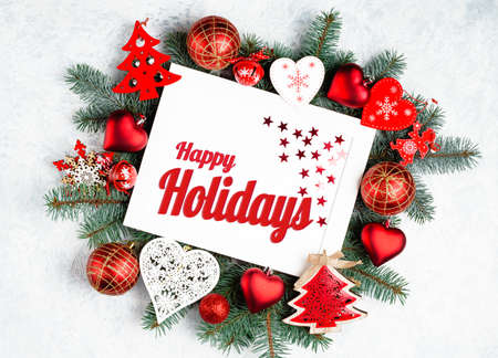 Happy Holidays Text with Holiday Evergreen Branches and photoframe New Year tree, red decorations Top view, flat lay Banco de Imagens