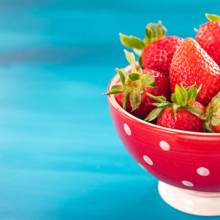 Fresh strawberries in bowl isolated on blue Stock Photo