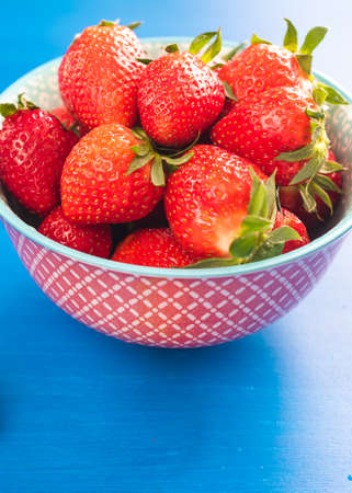 Fresh strawberries in bowl isolated on blue Фото со стока