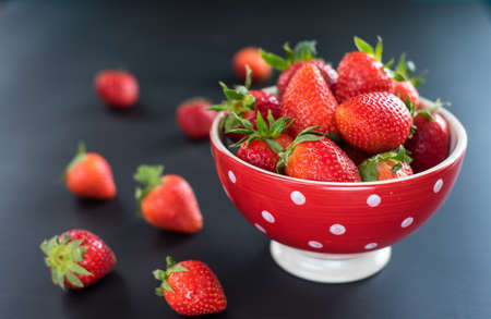 Delicious strawberries in bowl on black