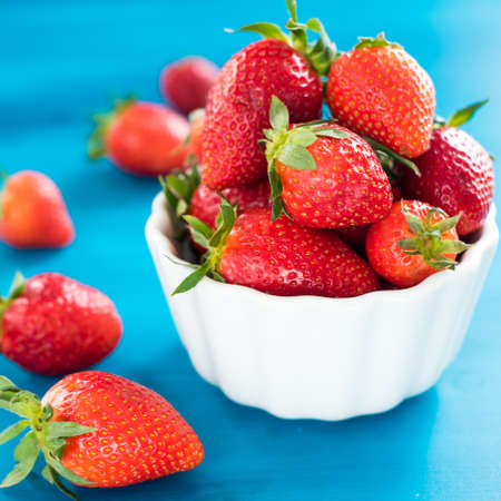 Fresh bright strawberries in a bowl top view on blue