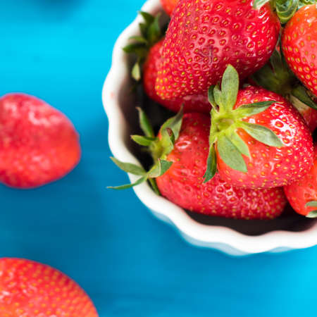 fresh bright strawberries in a bowl top view on blue background Stock Photo