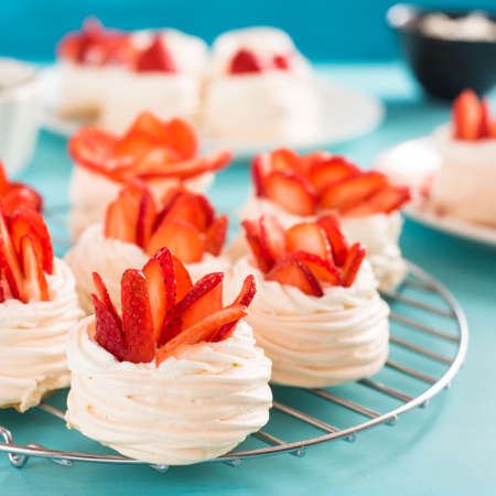 Beautiful pavlova cakes with strawberries on a blue background. Selective focus. Wedding morning. Meringue with cream. Stock Photo