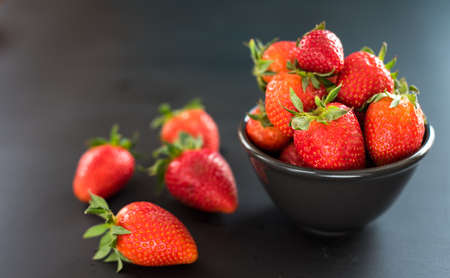 Delicious strawberries in bowl on black background. Stock Photo