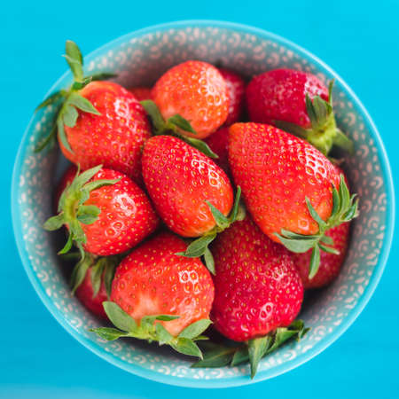 red strawberries in the plate isolated on wooden table Stock Photo