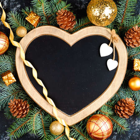 christmas background - decorations and fir branch on a table, a frame in the shape of a heart, top view, place for text, flat lay
