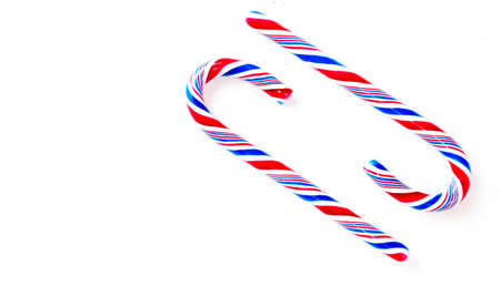 Candy canes on a white surface, top view