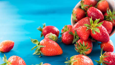 fresh bright strawberries spilled out of the bowl on blue background Stock Photo