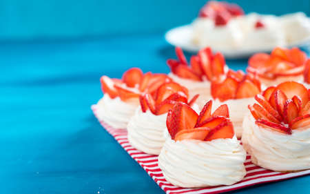 Beautiful pavlova cakes with strawberries on a blue background. Selective focus. Wedding morning. Meringue with cream. Imagens