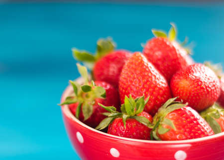 colorful ripe strawberries in a bright bowl on a blue background