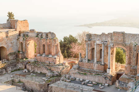 View of some columns and one arch in the scene of the greek theater in Taormina and a perspective of Giardini Naxos in the background Stock Photo