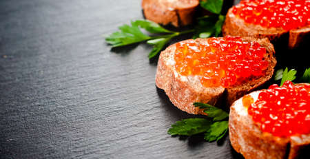 Red caviar on slate background. Selective focus