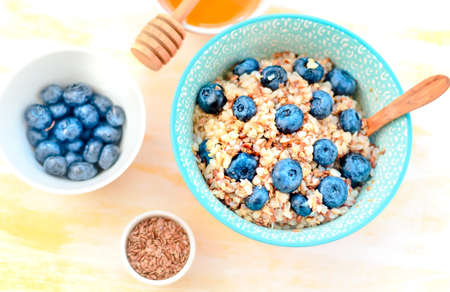 Healthy buckwheat porridge with blueberries on a wooden table, Perfect start of the day.