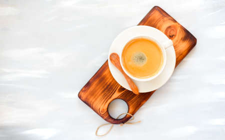 Cup of coffee with foam over a wooden gray table, top view
