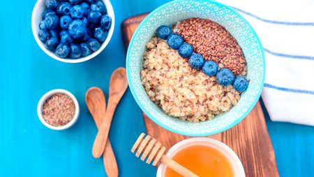 Healthy breakfast ingredients. Buckwheat blueberries mint honey on white wooden background, top view,