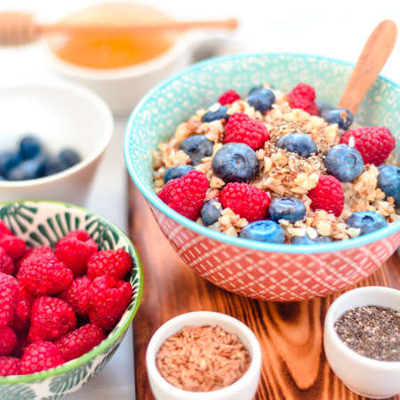 High protein healthy breakfast, buckwheat porridge with blueberries, raspberries, flax seeds and honey Closeup view Stockfoto - 127508678