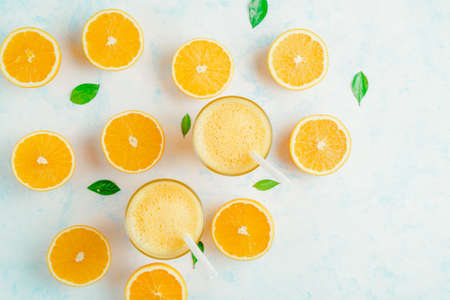 Top view of cold orange smoothie and orange fruits with green leaves isolated on white background. Stockfoto - 127508736