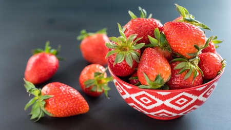 Delicious strawberries in a bowl on black background.