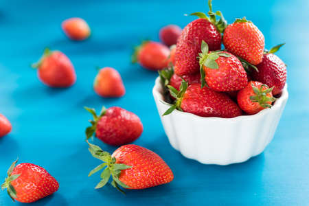 fresh bright strawberries in a bowl top view on a blue background Stockfoto - 128261174