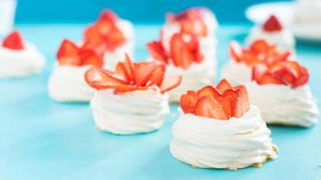 Beautiful pavlova cakes with strawberries on a blue background. Selective focus. Tasty sweet breackfast. Wedding morning. Meringue with cream. Stockfoto - 128261178