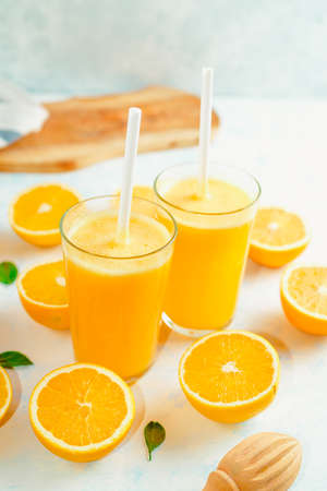 Top view of orange smoothie and orange fruits with green leaves on white background. Stockfoto