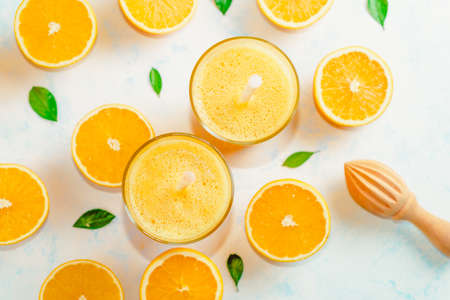Top view of orange smoothie and orange fruits with green leaves on white background. Stockfoto - 128261181