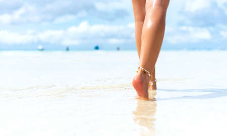 Beach travel concept. Sexy Legs on Tropical Sand Beach. Walking Female Feet. Closeup Stockfoto - 128261186