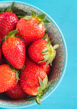Juicy, ripe strawberries in a colorful turquoise bowl, top view