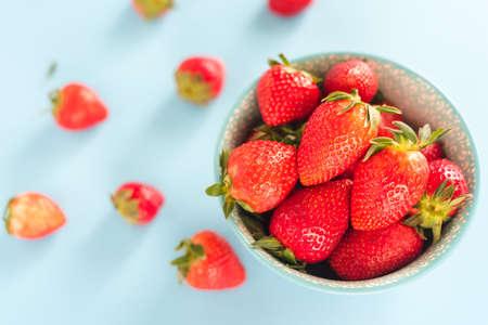 Fresas maduras y jugosas en un tazón de fuente de color turquesa, vista superior