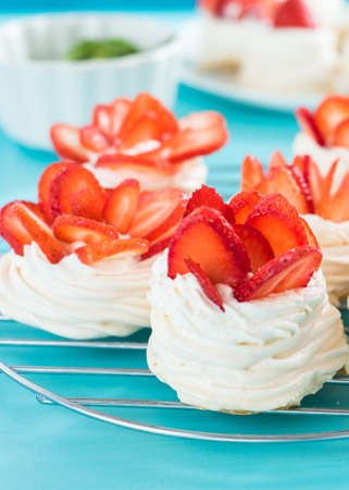 Beautiful pavlova cakes with strawberries on a blue background. Selective focus. Tasty sweet breackfast. Wedding morning. Meringue with cream. Stockfoto - 128261194
